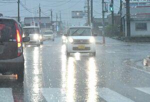 激しく降る雨の中、ライトをつけて走行する乗用車=25日午前8時15分ごろ、佐賀市久保田町