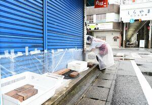 店舗シャッターに浸水を防ぐビニールを貼る女性=6日午後、佐賀市白山