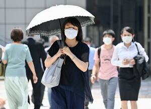 真夏日となった名古屋市で、日傘を差して歩く女性=5日午後