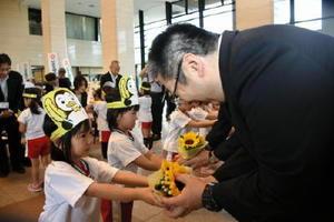 社会を明るくする運動のシンボル・ヒマワリの花束を市町の代表者に渡す園児=県庁県民ホール