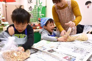 大豆をつぶす作業を楽しむ子どもたち=佐賀市のコープ佐賀新栄店
