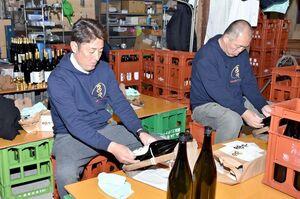 出荷に備え、瓶にラベルを貼る多久未来プロジェクトのメンバー=多久市の東鶴酒造