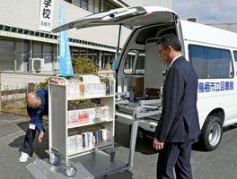 新しい移動図書館車のリフトでブックトラックを下ろしてみせるスタッフ=鳥栖市役所