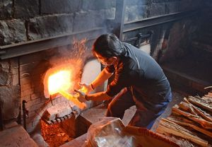 火の粉を飛ばし、薪を投げ入れる職人。薪は赤松を使う=有田町の今右衛門窯