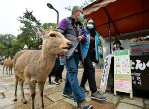 マスク姿で奈良公園を訪れた人たち。右は鹿せんべい販売所=1月29日、奈良市