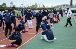 両足で白線の左右を素早く跳ぶ力のテストに挑戦する中学生たち=佐賀市の県総合運動場陸上競技場