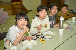 消防団員が時間をかけて調理したちゃんこ鍋に舌鼓を打つ地元の子どもたち=佐賀市の日新公民館