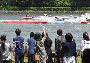 第1ターンマークで旋回する選手たちを近くで見守る参加者たち=唐津市原のボートレースからつ
