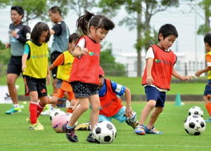 サガン鳥栖のアカデミーコーチ陣に指導を受けながら、ドリブル練習などに取り組む子どもたち=鳥栖市陸上競技場