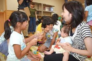 遊具などを手に赤ちゃんと楽しそうに遊ぶ3年生=武雄市の武雄小