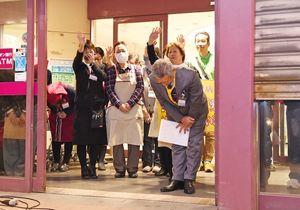 閉店を見届ける来場者へ手を振り、シャッターが閉まるまで感謝する従業員ら=28日午後8時ごろ、上峰町のイオン上峰店