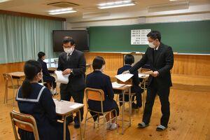 特別選抜試験で問題用紙を配る職員=佐賀市の佐賀北高校