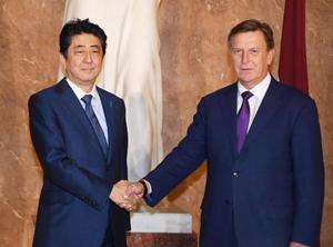 ラトビアのクチンスキス首相(右)の出迎えを受け握手する安倍首相=13日、リガ(共同)