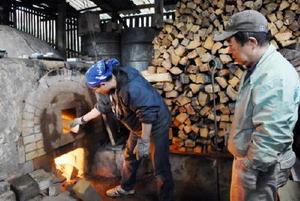 初窯出しに向けて、登り窯をたく溝上藻風さん(右)と良博さん=伊万里市大坪町の今岳窯