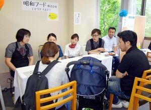 夫や子連れで参加し、参加企業(奥)から説明を受ける参加者=武雄市の森のリゾートホテル
