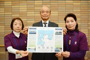 作製した「まつら半島を囲む10の島島めぐりマップ」を掲げる執行勉さん(中央)ら=唐津市二タ子の高齢者ふれあい会館りふれ