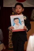 愛らしい表情を捉えた似顔絵を手にする園児=佐賀市の日新こども園