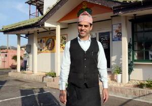 「祐徳稲荷神社は社殿の朱色が美しい」と語るレシャムラル・カンデルさん=鹿島市のインドカレー店「プルニマ」