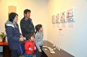 グラフィックデザイナーたちの発想豊かな作品を楽しむ来場者=佐賀市本庄町の高伝寺前村岡屋ギャラリー