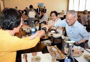 唐津焼のぐい飲みに地酒を注ぐツアー客=唐津市東唐津の旅館「松の井」