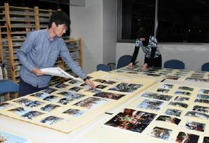 唐津くんち写真展で展示する写真パネルの準備を進めるスタッフ=佐賀市の佐賀新聞社