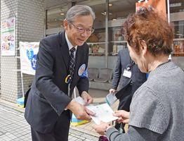 「パートナーデー」のメッセージカードを配る市職員=佐賀市の佐賀玉屋前
