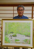 受賞作「奥入瀬夏景色」を手にする毛利俊治さん=基山町の自宅