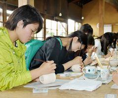 筆を使い、黙々と絵付けする生徒ら=嬉野市塩田町の志田焼の里博物館