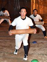 丸太を使ったトレーニングに汗を流す伊万里の選手たち=同校グラウンド