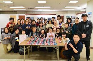 宮城県気仙沼市に贈る手作りのひな人形100組を制作した参加者たち(提供写真)=佐賀市の佐賀玉屋