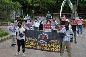 3本の指を立て、軍に抗議する意思を示す県内在住のミャンマー人ら=佐賀市駅前中央の駅前まちかど広場