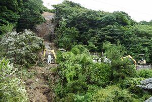 JR佐世保線の線路をふさいだ樹木や土砂を重機で撤去する作業員=2017年7月、有田町赤絵町
