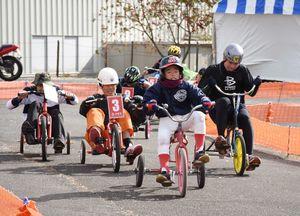 三輪車で熱いレースを繰り広げる選手たち=上峰町の三田川自動車学校跡地