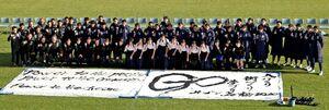 鳥栖高書道部が揮毫した2020シーズンのスローガン「GO」と、記念撮影するサガン鳥栖の選手ら=鳥栖市の駅前不動産スタジアム