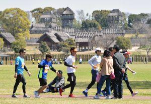 弥生の風景をバックに力走するランナー=吉野ケ里歴史公園