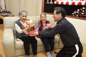 掛川施設長(右)から花をプレゼントされ、喜ぶ福田さん(中央)と太田さん=武雄市北方町のデイサービスほほえみ
