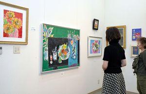 明るい色で描かれた、花や果物などのアクリル画や油絵42点が並ぶ=吉野ヶ里町のギャラリーアートえる