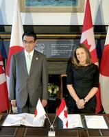 自衛隊とカナダ軍の物品役務相互提供協定の署名に臨む河野外相(左)とカナダのフリーランド外相=21日、カナダ・トロント(共同)
