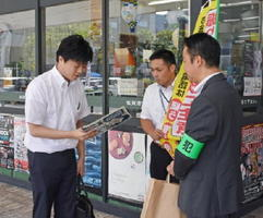チラシを配り、注意喚起を促す会議出席者=佐賀市のJR佐賀駅
