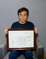 日本記録を打ち立てた大会の賞状を手にする岩永義次さん