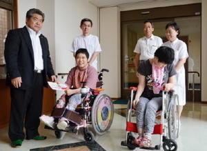 マリトピア会の中島新太郎会長(左)から寄付金を受け取る松本愛さん(前列左から2人目)=佐賀市の佐賀整肢学園(提供)