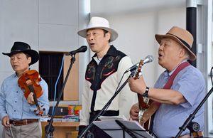 地元のももみやバンドと一緒に歌う大須賀ひできさん(中央)=有田町役場