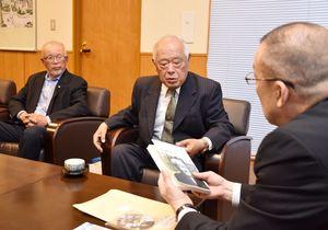 江里口秀次小城市長(右)に高田保馬博士の伝記、DVDの完成を報告する顕彰会の上野保明会長(中央)ら=小城市役所
