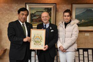 横尾俊彦多久市長(左)にサンマリノの絵を贈ったマンリオ・カデロ駐日大使と妻のエリザベスさん