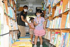 自動車図書館「ブーカス号」に乗り込み、車内の両側に高く積まれた本を眺める子どもたち=佐賀市立図書館