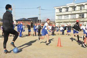 赤司大輔コーチ(左)に見守られ、ゲームに取り組む5年生=小城市の牛津小