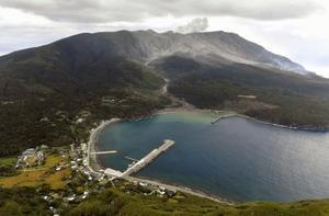 新岳(奥中央)が爆発的噴火を起こした鹿児島県・口永良部島=17日午前11時56分(共同通信社ヘリから)