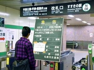 地震の影響で運行が止まった地下鉄すすきの駅で、案内板を見る男性=21日午後10時40分、札幌市中央区