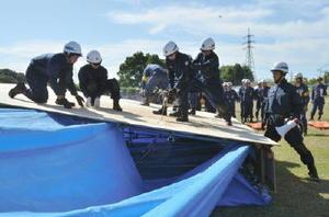 チェーンソーで倒壊した建物に穴を開け、人命救助にあたる警察署員や消防団員たち