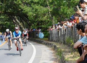 声援を受けながら、自転車で疾走する選手たち=昨年6月、唐津市の虹の松原